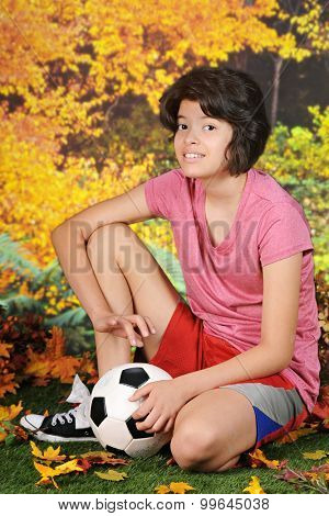A pretty Hispanic girl happily kneeling with her soccer ball on a warm autumn day.