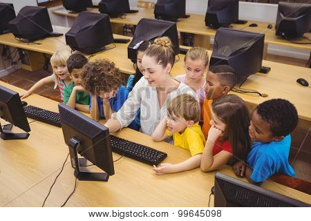 Teacher showing students how to use a computer at the elementary school