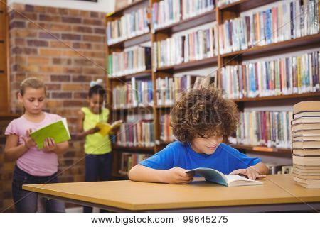 Happy pupil reading a library book at the elementary school