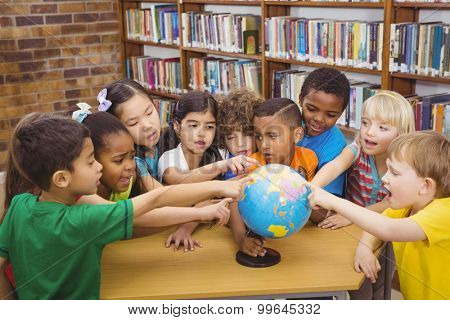Students pointing at a globe at the elementary school