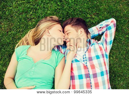 holidays, vacation, love and friendship concept - smiling couple lying on on grass and kissing in park
