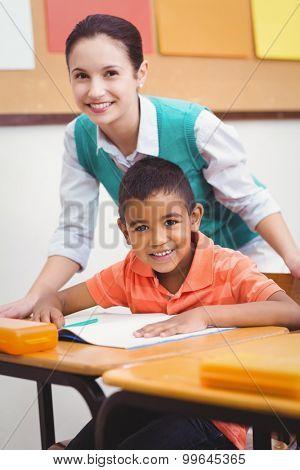 Teacher helping a little boy during class at the elementary school