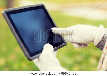 technology, advertisement and people concept - close up of hands in autumn gloves holding tablet pc computer with black blank screen outdoors