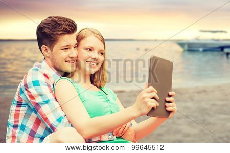 vacation, holidays, travel, technology and love concept - smiling couple with tablet pc computer taking selfie over sunset beach background