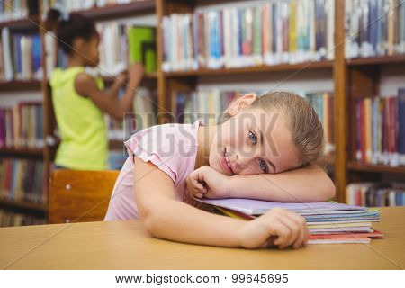 Student resting her head on some books at the elementary school library