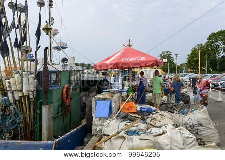 DZIWNOW - AUGUST 16: People buy fresh fish directly from the fishing boat on 16 August 2015 in Dziwnow, Poland.