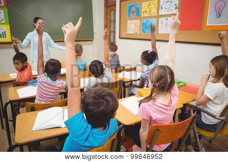 Pupils raising their hands during class at the elementary school