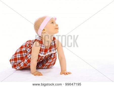 Portrait Of Cute Baby In Dress With Headband Crawls And Looks Up