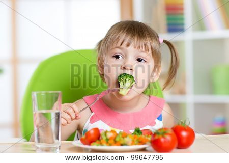 Cute little girl eats vegetable salad using fork