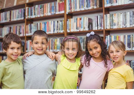 Pupils smiling at camera in library at the elementary school