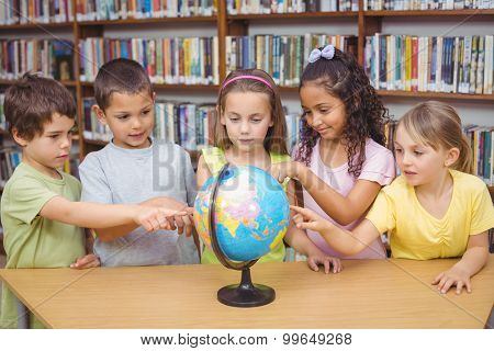 Pupils looking at the globe in library at the elementary school