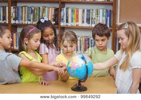Pupils in library pointing to globe at the elementary school