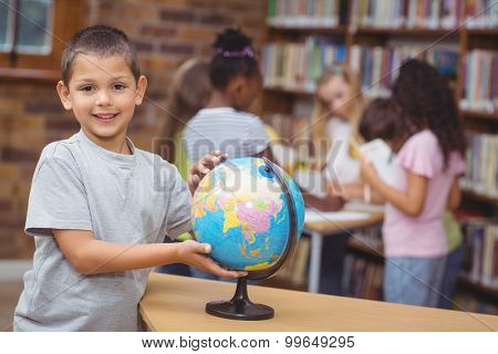 Pupil in library with globe at the elementary school
