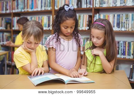 Pupils reading book together in library at the elementary school