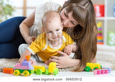 child boy and mother playing together with toys at home
