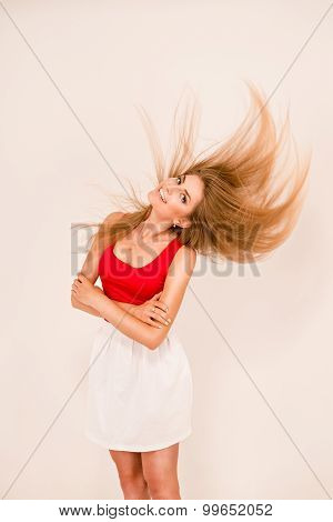 Beautiful Girl On A White Background Smiling And Her Hair Up In The Air