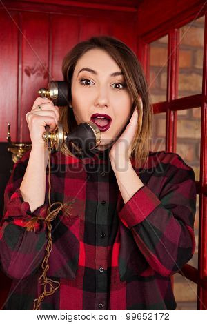 Beautiful Young Girl In Casual Style Standing In A Red Telephone Booth Keeps The Handset