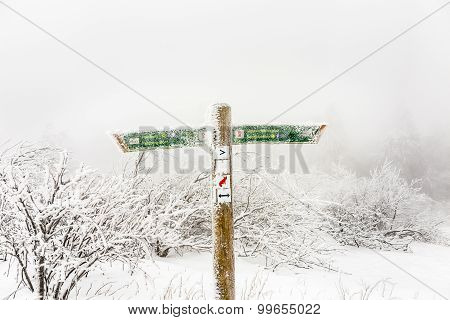 Post With Signs For Orientation And Distances In Snow Blizzard At The Summit Of  The Feldberg