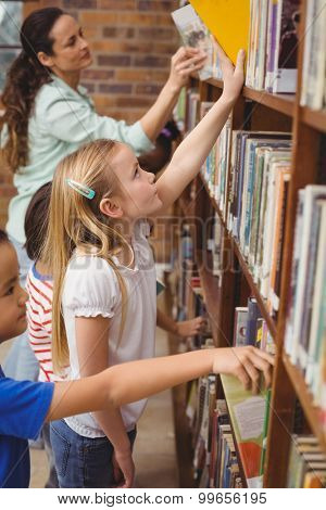 Pupils taking books from shelf in library at the elementary school