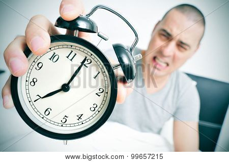 an angry young caucasian man in bed holds in his hand his alarm clock set at seven in the morning