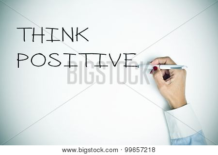 closeup of a young woman writing the sentence think positive with a pen on a white surface, slight vignette added