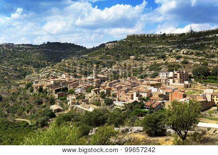 a panoramic view of Vilanova de Prades, a small town in Prades Mountains, in Spain, with the Serra de la Llena range in the background