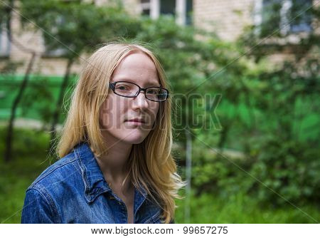 Outdoor portrait of a teenager girl in jeans jacket and glasses.
