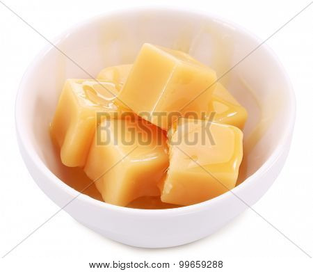 Caramel candies in the white dish. White background. Clipping path.