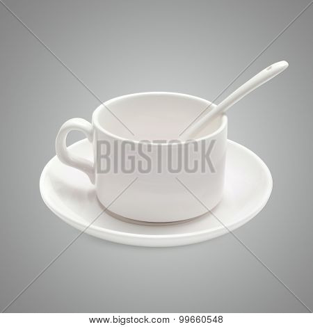 White coffee cup with a spoon on the saucer ion gray background