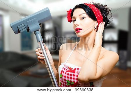 Amazed beautiful pinup lady holding hoover in apartment