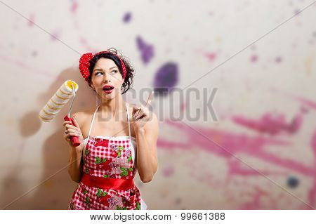 Excited young pin up housewife in apron with paint roller