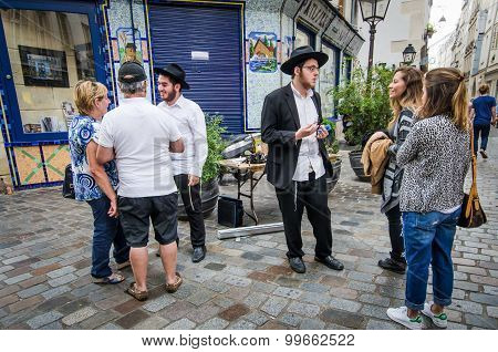 Street scene in Marais with Orthodox Jewish young men talking with tourists