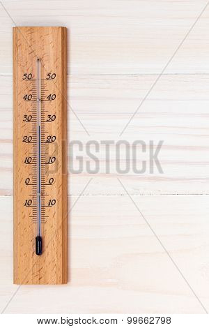 Thermometer On Wooden Background
