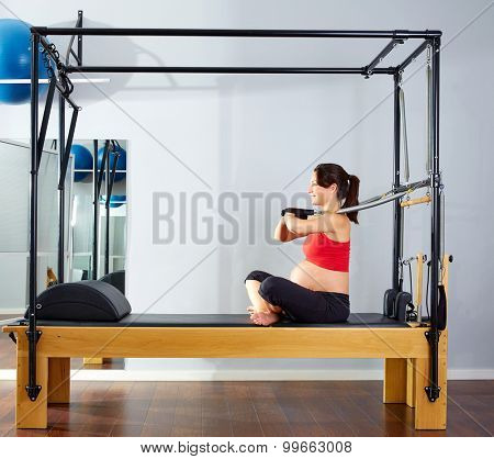 pregnant woman pilates reformer cadillac arms exercise workout at gym