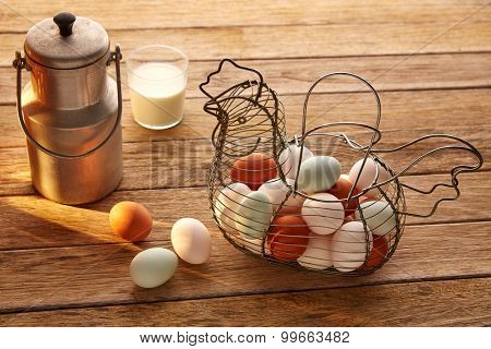 Eggs and milk in a vintage hen shape basket on wood with blue easter white and brown
