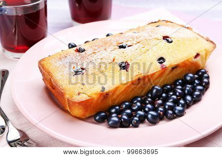 Freshly baked cake with black currants in pink plate, closeup