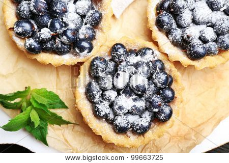Delicious crispy tarts with black currants on parchment, top view