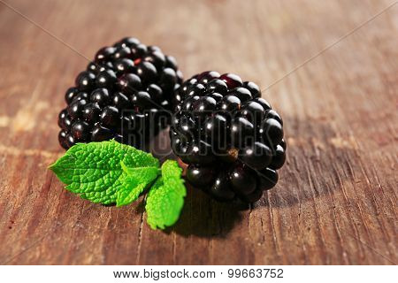 Ripe blackberries with green leaves on wooden background