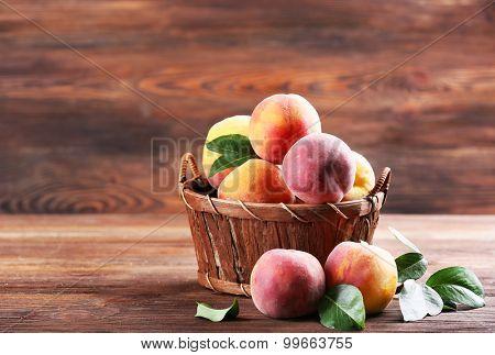 Fresh peaches in wicker basket on wooden background