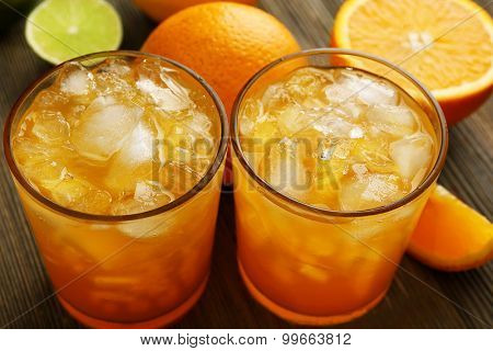 Glasses of orange juice on wooden table, closeup