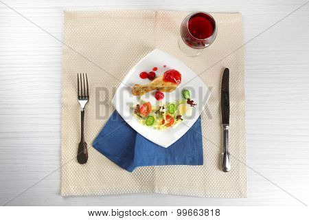 Dish of baked chicken leg and vegetable salad in white plate with glass of wine on table with napkin, top view