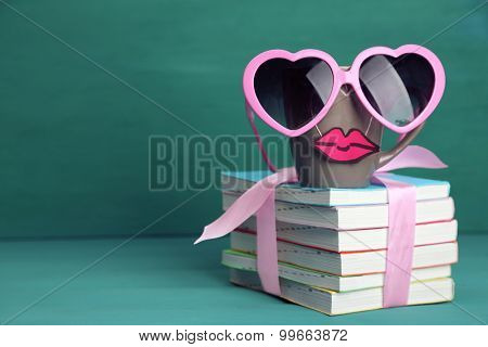Books and cup with lips on colorful background