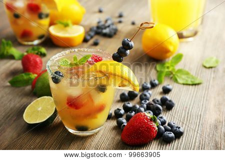 Glass of berries juice with lemon on wooden table, closeup