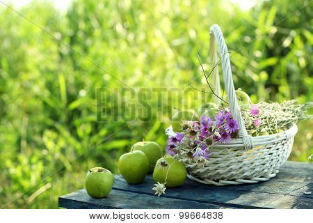 Green apples with bouquet of wildflowers on wooden table, outdoors