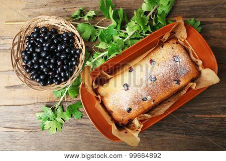 Freshly baked cake with black currants in brown pan on wooden table, top view