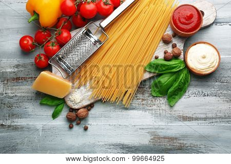 Pasta spaghetti with tomatoes, cheese and basil on color wooden  background