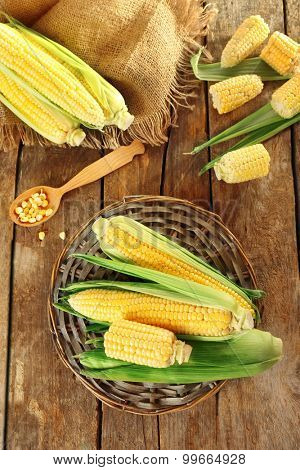 Fresh corn on cobs on wicker mat on wooden table, top view