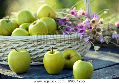 Green apples with bouquet of wildflowers on wooden table, closeup