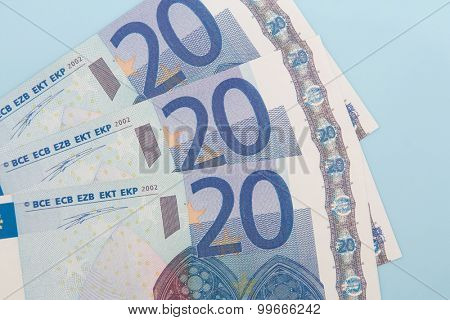 Three twenty euro notes on light blue background