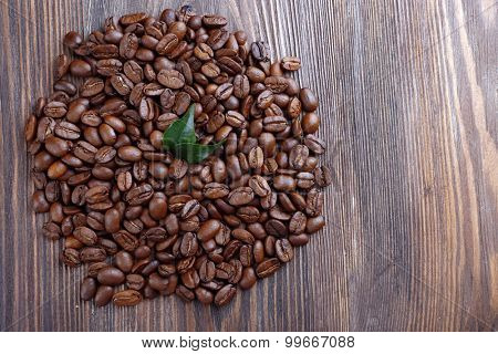 Coffee beans with leaves on wooden table close up